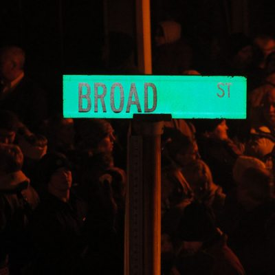 A sign for Broad Street in front of people