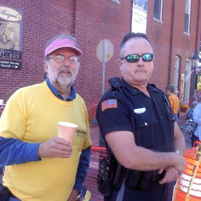 A man in a yellow shirt standing next to a police officer